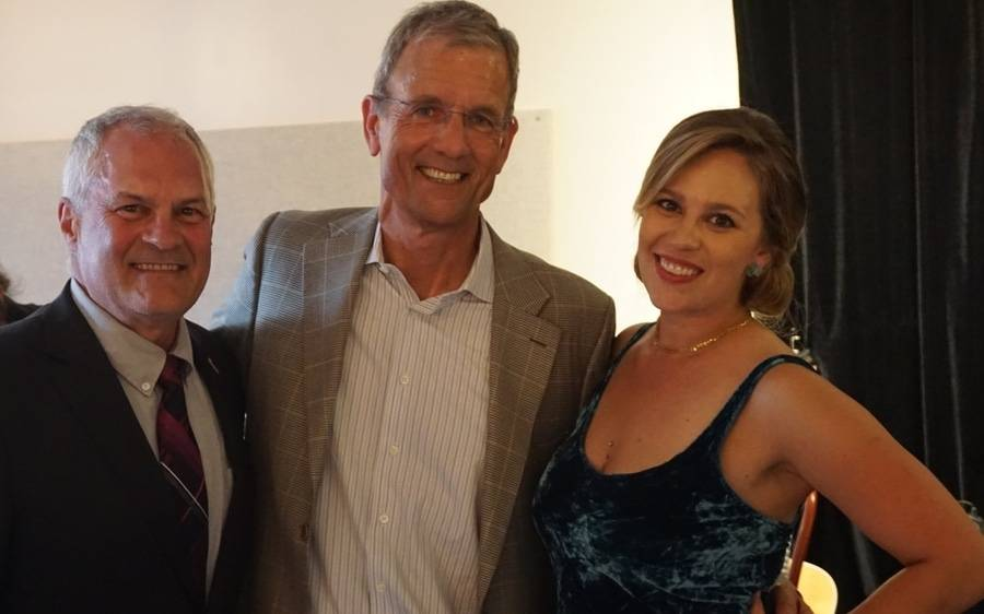 Two mature men and a mature woman enjoy a moment together at the Roxy Encinitas cancer care benefit.