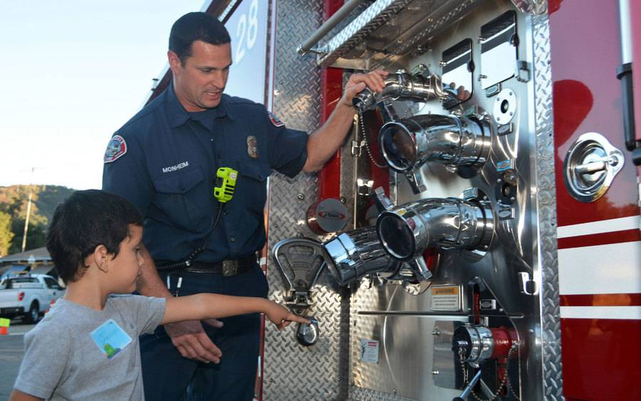 A firefighter shows a child the lifesaving equipment on a fire truck at the Annual Trauma Expo at Scripps Memorial Hospital La Jolla.