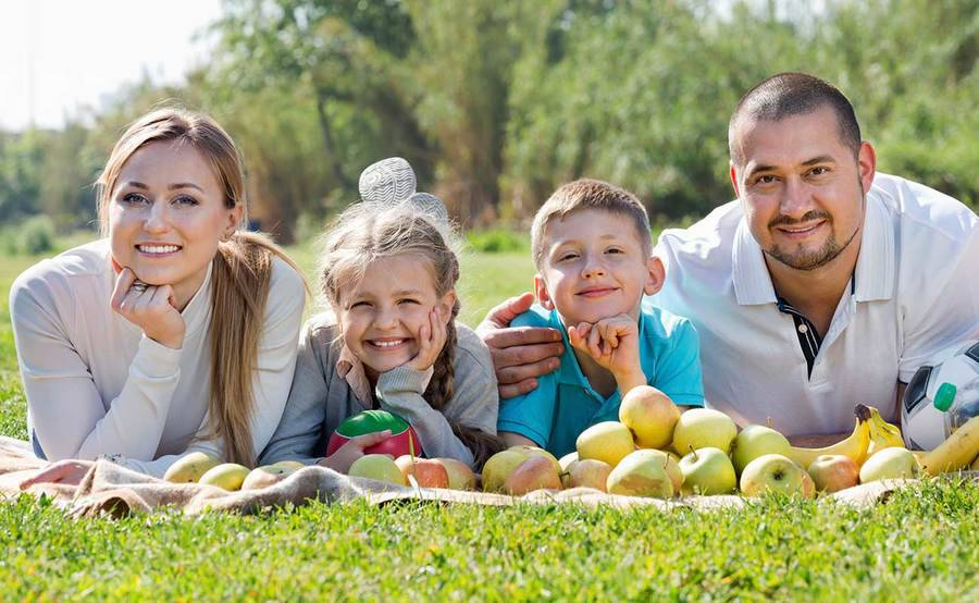 A smiling young family lays on a picnic blanket, representing a range of skin care and dermatology needs.