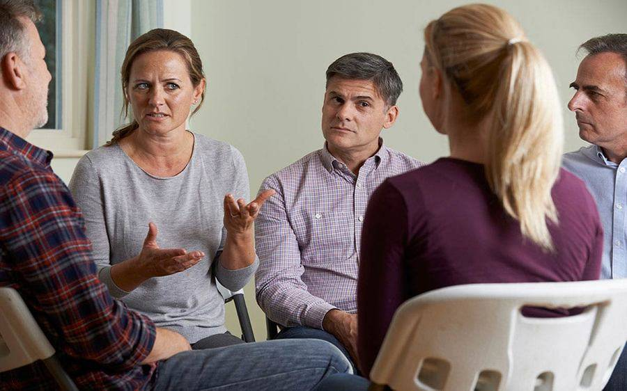 A woman talks to other adults in a support group.