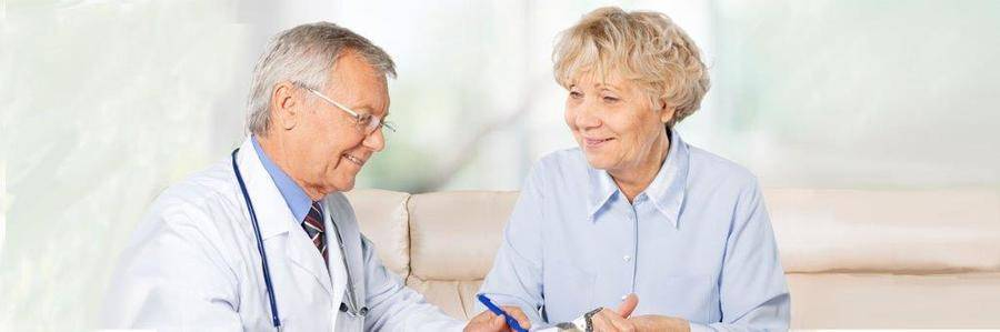 A relaxed elderly woman talks with her physician while seated on a couch in an indoor clinical setting.