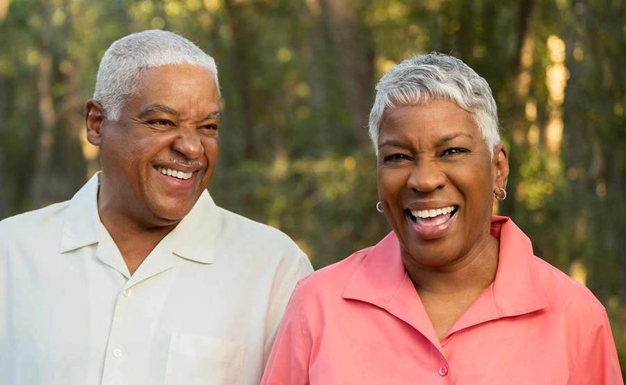 A smiling middle-aged African-American man and woman represent the full life that can be led after digestive cancer treatment.