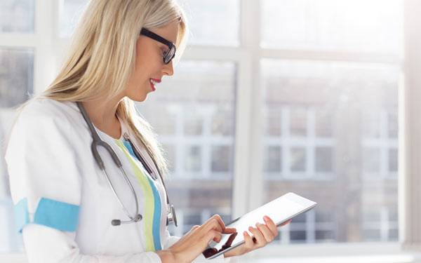 Doctor looking at tablet-600×375