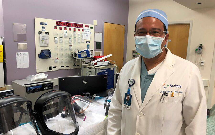 Dr. Juan Tovar stands next to face shields for coronovirus at Scripps.