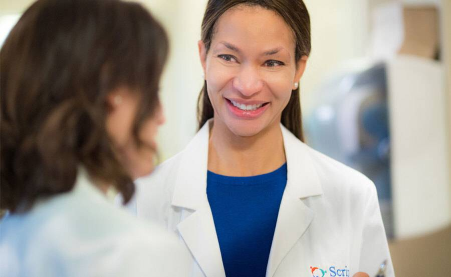 Dr. Rio Dickens- Celestin, Internal Meidicne, Scripps Clinic, smiling while talking to a patient.