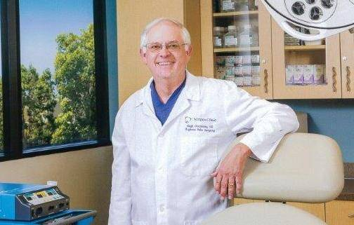 Hubert Greenway, MD, stands in a doctor's office after receiving a major skin cancer award.