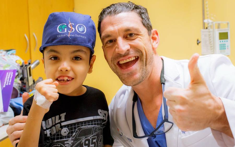 A child patient and Gregory Mundis, MD, an orthopedic surgeon, raise their arms in approval.