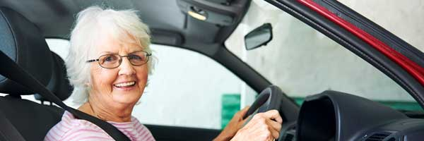 An elderly woman sits in the driver's seat with her hands on the steering wheel as part of a driving rehabilitation session.