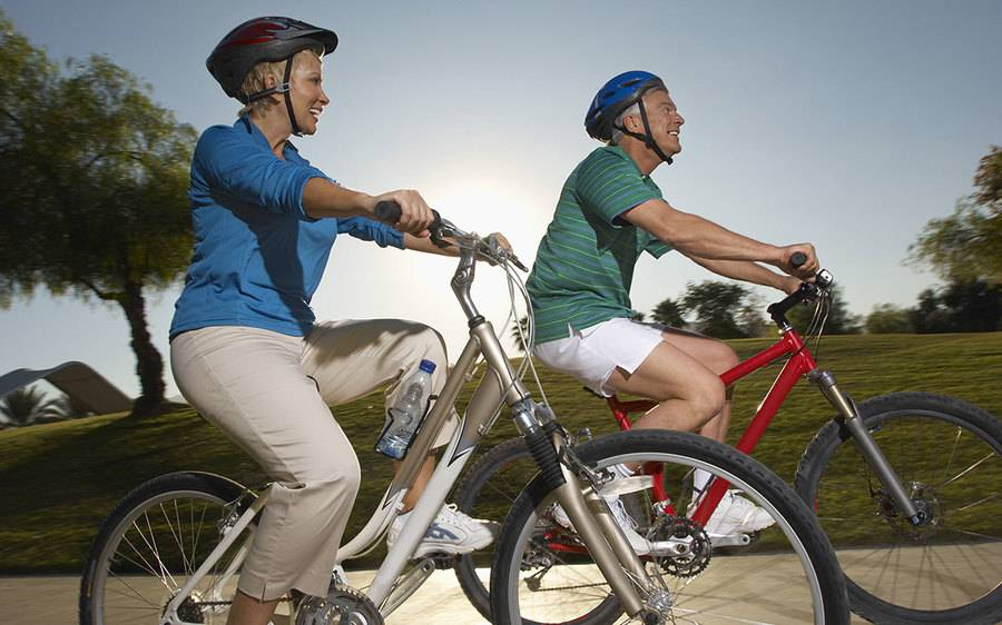 A couple enjoy a bike ride on a sunny day.