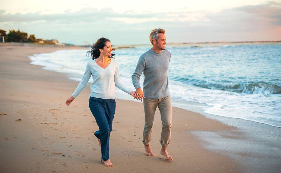Two smiling middle-aged adults hold hands while walking on the beach, representing Scripps Executive Health services in San Diego..