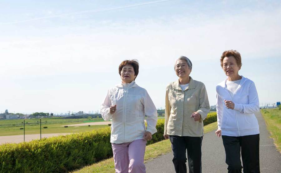 Three middle-aged women walking outdoors for exercise to lose weight and keep their weight stable.