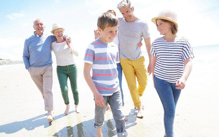A family of grandparents, parents and children walk on a sunny beach, representing the importance of balance and fall prevention during the summer.