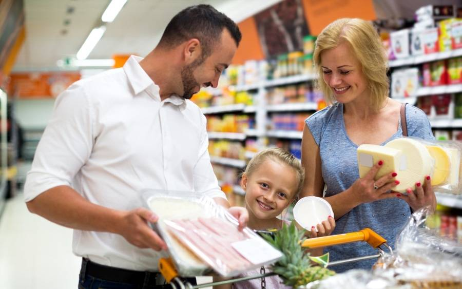 A father, mother and young daughter with celiac disease shop for gluten free foods.