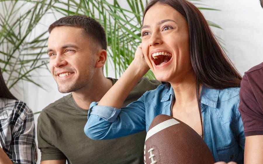 Young couple watches football game on TV with lots of excitement. Both are in fantasy football leagues.