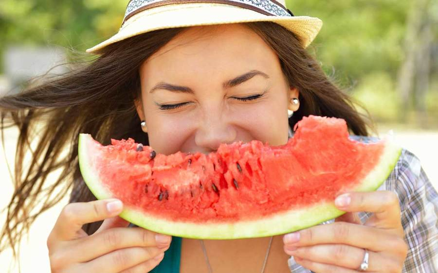 A happy woman wearing a sun hat bites into a big watermelon wedge in a sunny outdoor setting