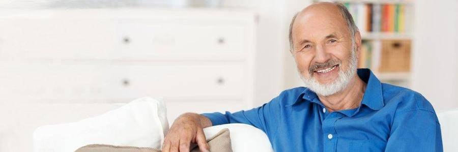 A smiling elderly gentleman relaxes on a white couch in a pleasant indoor setting.