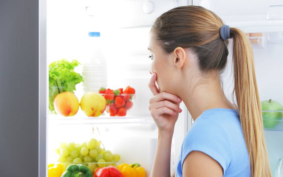 Woman with food cravings finds healthy foods in her refrigerator.