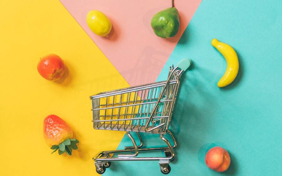 A grocery shopping cart surrounded by vegetables and fruits.