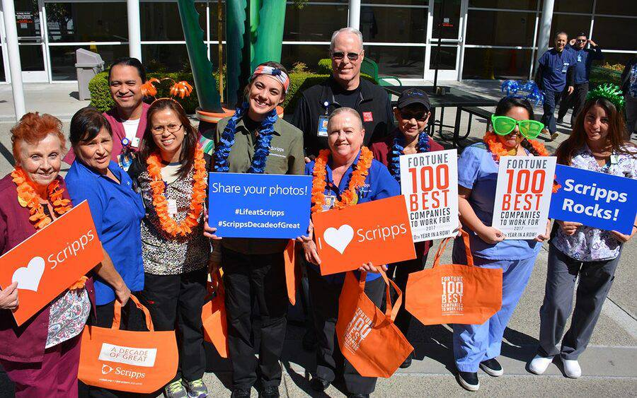 Scripps Health CEO Chris Van Gorder stands with employees holding signs about Fortune 100 Best Companies to Work For.