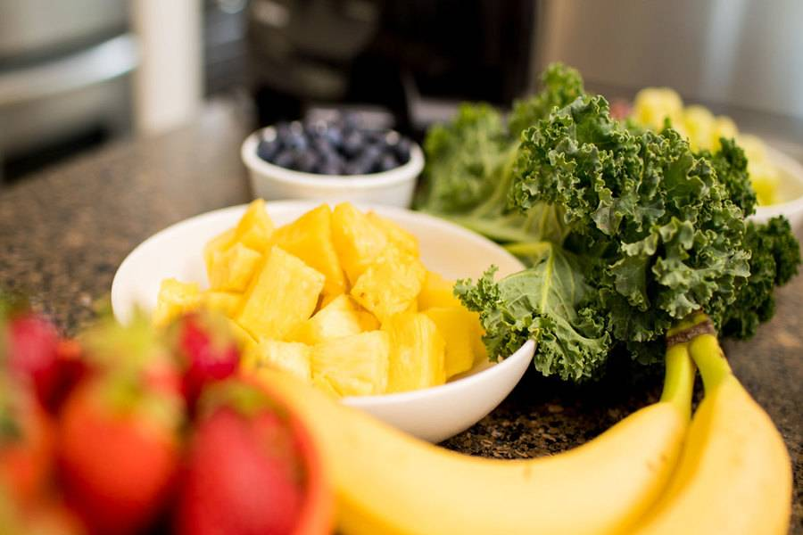Fresh kale, cut pineapple and other healthy fruits and vegetables. Scripps Health.