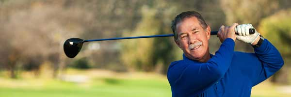 Garry Collins takes a swing on a golf course after undergoing a successful hip replacement procedure.
