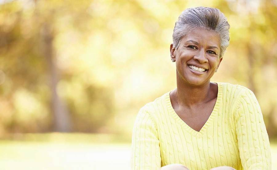 A smiling African-American woman represents the full life that can be led after gastrointestinal carcinoid tumor treatment.