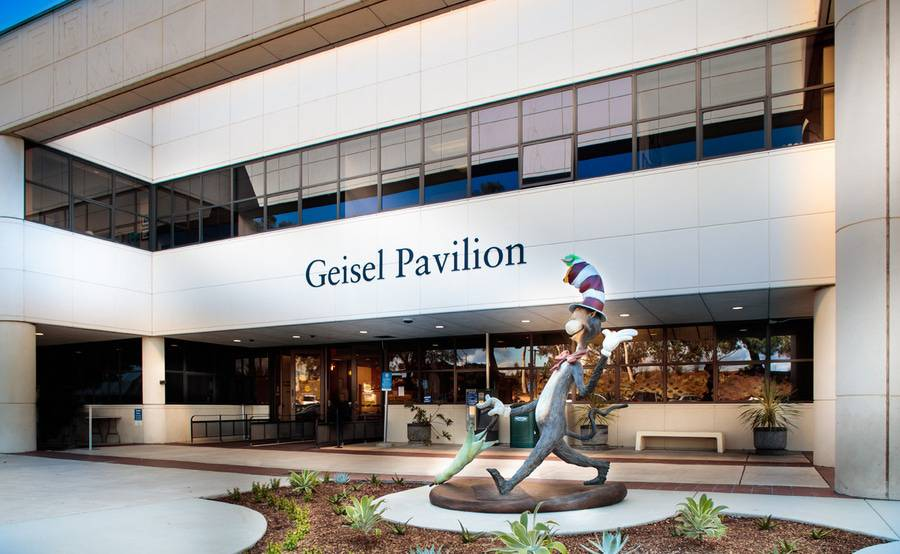 The outside of Geisel Pavilion, which houses Scripps Clinic Torrey Pines Urgent Care, with Dr. Seuss Cat in the Hat statue to the right of the doors.