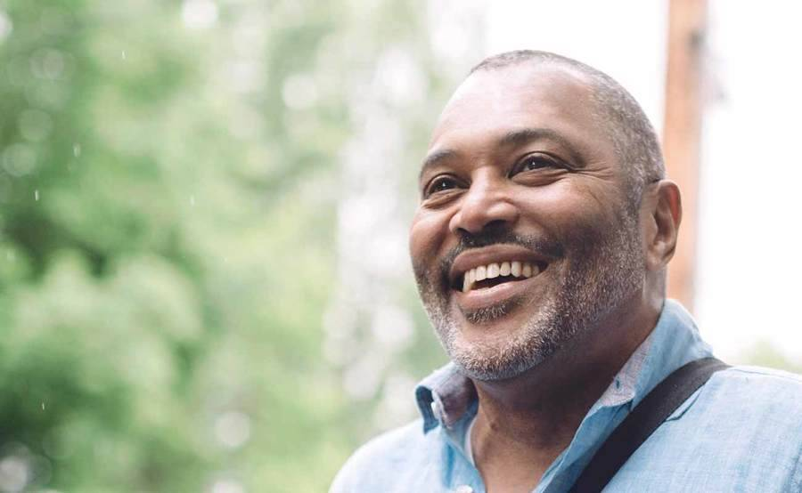 A smiling middle-aged African-American man represents the full life that can be led after treatment for genitourinary cancer.