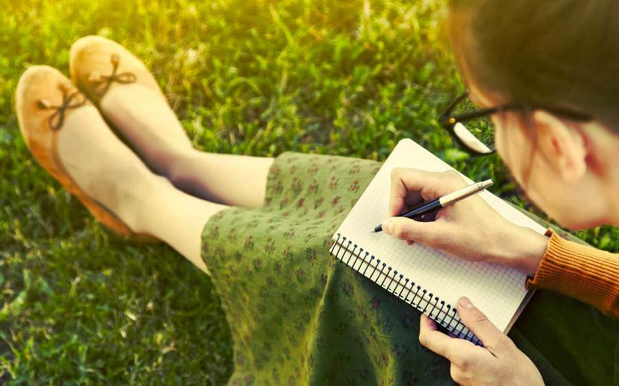 A young woman in colorful clothing sits on the grass writing in her journal