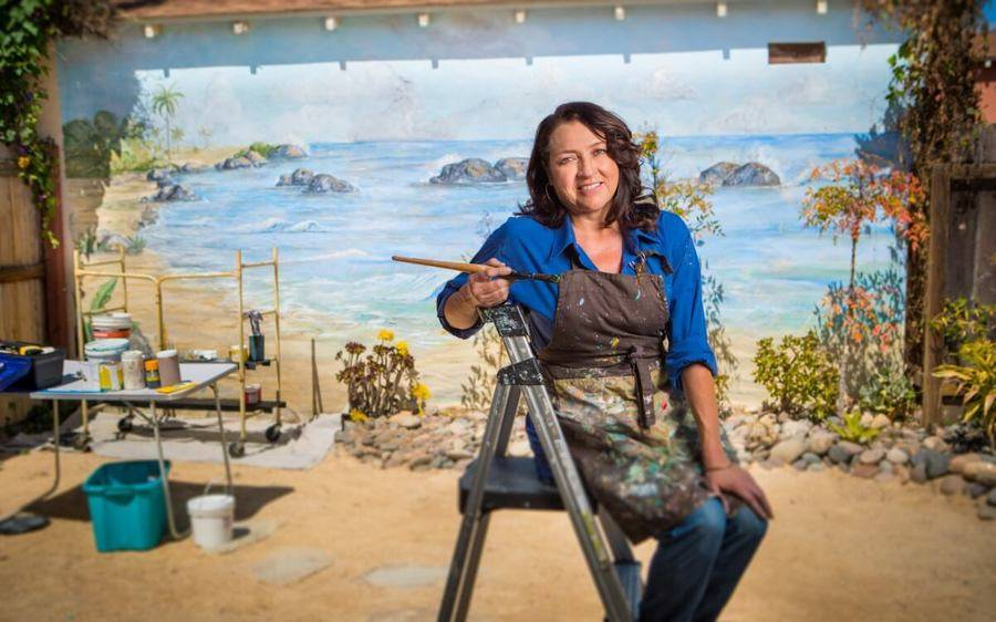 Mural artist, Gloria Favela, sits on a step ladder in a paint-splattered apron with a paint brush in her hand.