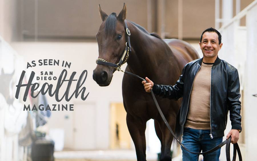 Hall of Fame jockey Victor Espinoza stands next to a racehorse, grateful to be back on his feet after Scripps Health treated his severe spinal cord injury.