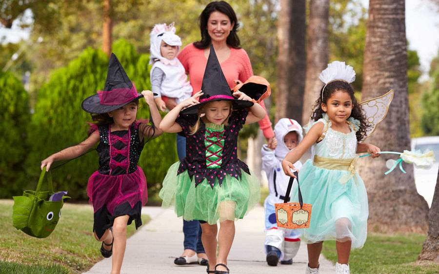 A young mother closely watches a group of kids dressed up for Halloween as one of 13 ways to keep them safe.
