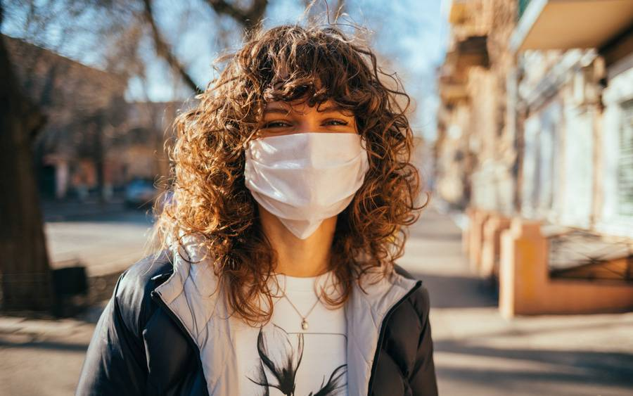 A young woman wears a face mask on a city street, representing the public service campaign #MaskUp.