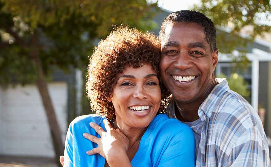 A smiling middle-aged African-American couple represents the full life that can be led after treatment for head and neck cancer.
