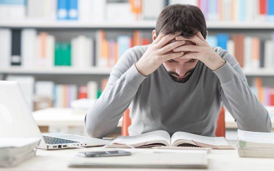 A man with a headache pauses from his studies to rest his head in his hands in a library setting