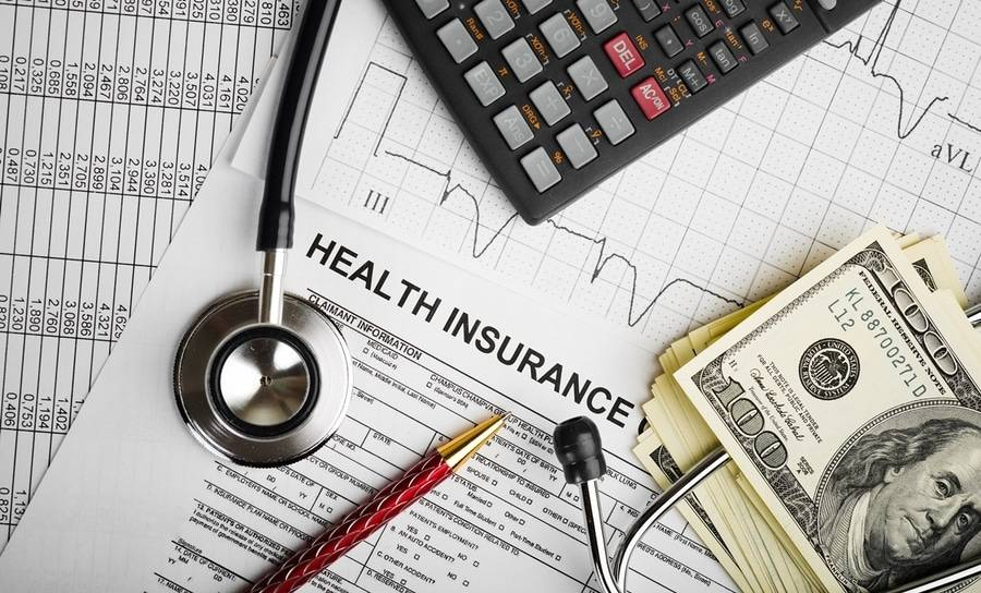 A stack of money, pen, calculator and stethoscope lie on health insurance forms depicting disruption in healthcare.