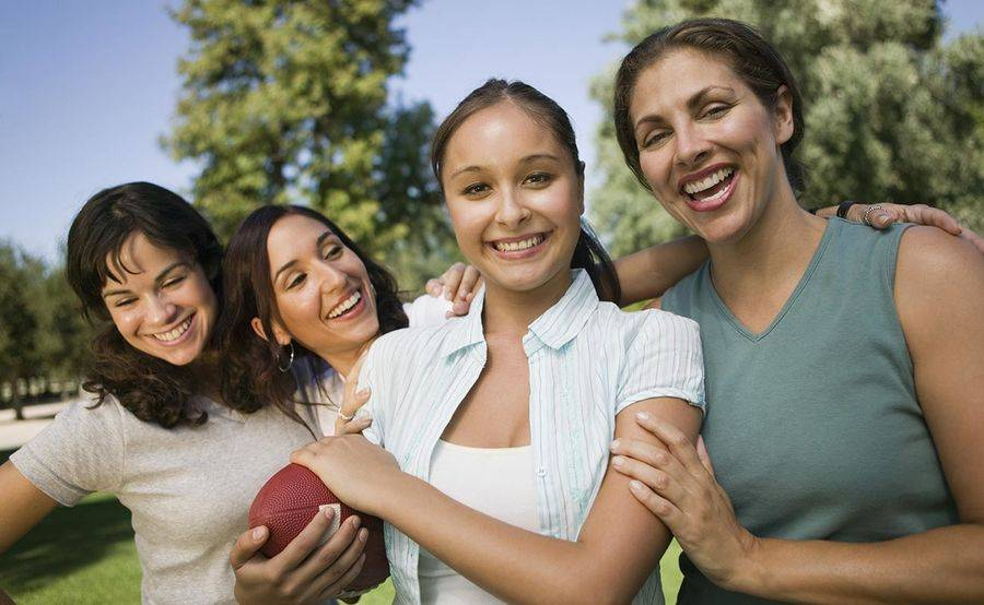 A woman holds a football and is hugged by three friends, representing the importance of staying active and making healthy lifestyle choices