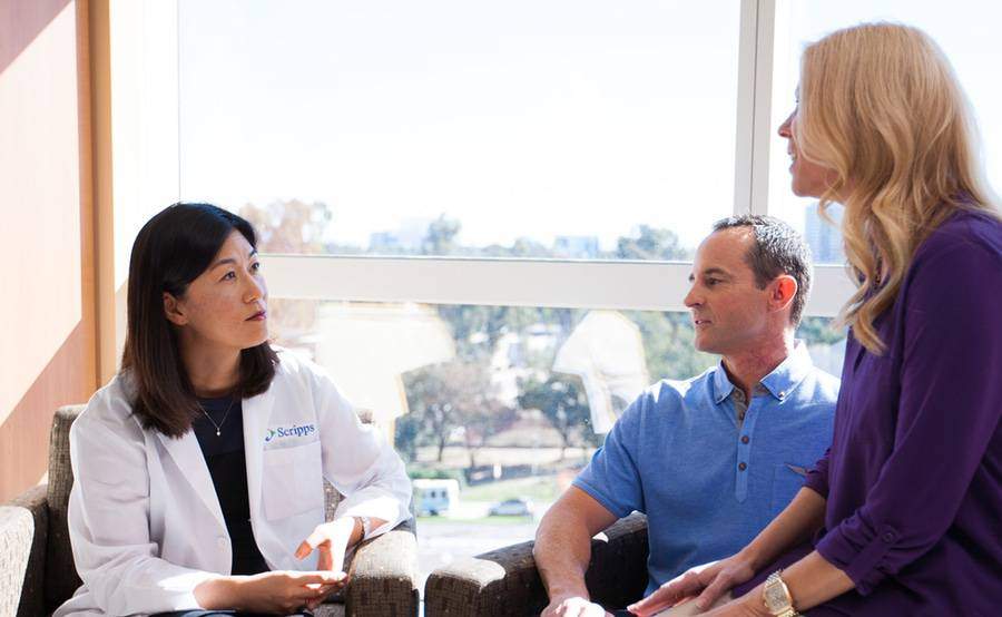 Dr. Kiyon Chung sits with a man and a woman in a bright, sunny room.