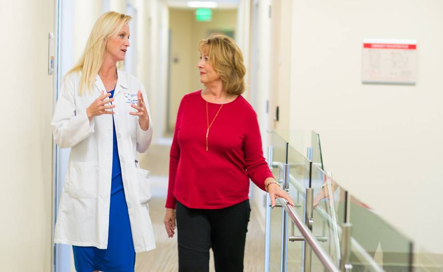 Dr. Christina Adams walks with a person in a hallway, representing the personal cardiology care at Scripps.