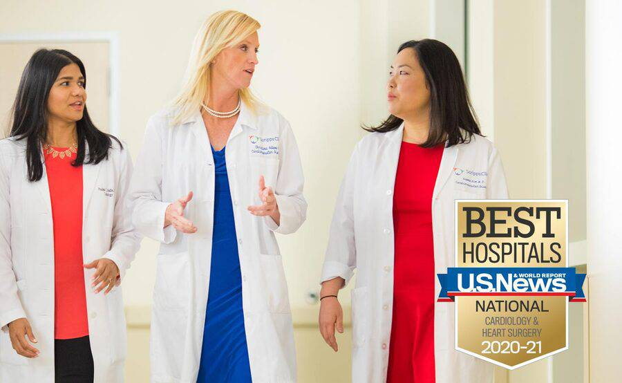Three female cardiologists talking in a hospital hallway represent the expertise in women's heart care at Scripps.
