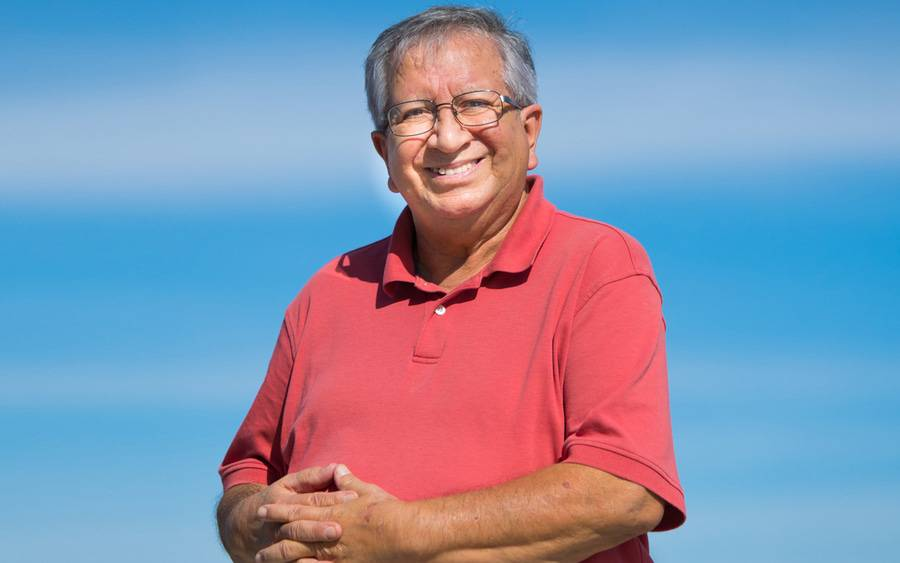 Volunteer and diabetes patient Hector Nunez smiles against a blue sky.