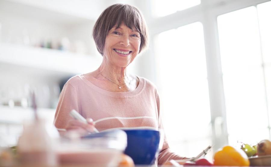 A woman smiles while preparing food in her home, representing how surgery at Scripps for gynecologic conditions can help improve quality of life for women.