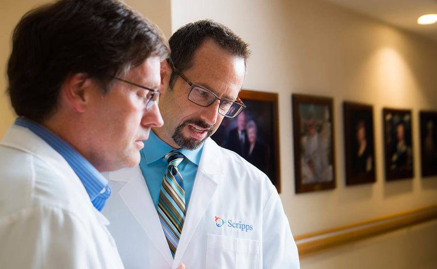 Two Scripps Health organ transplant experts have a conversation in a medical location hallway.