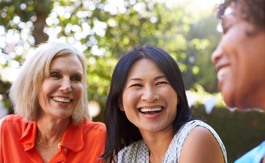 Three women smiling outdoors, represents the comfort of receiving great OBGYN care at Scripps Health in San Diego.