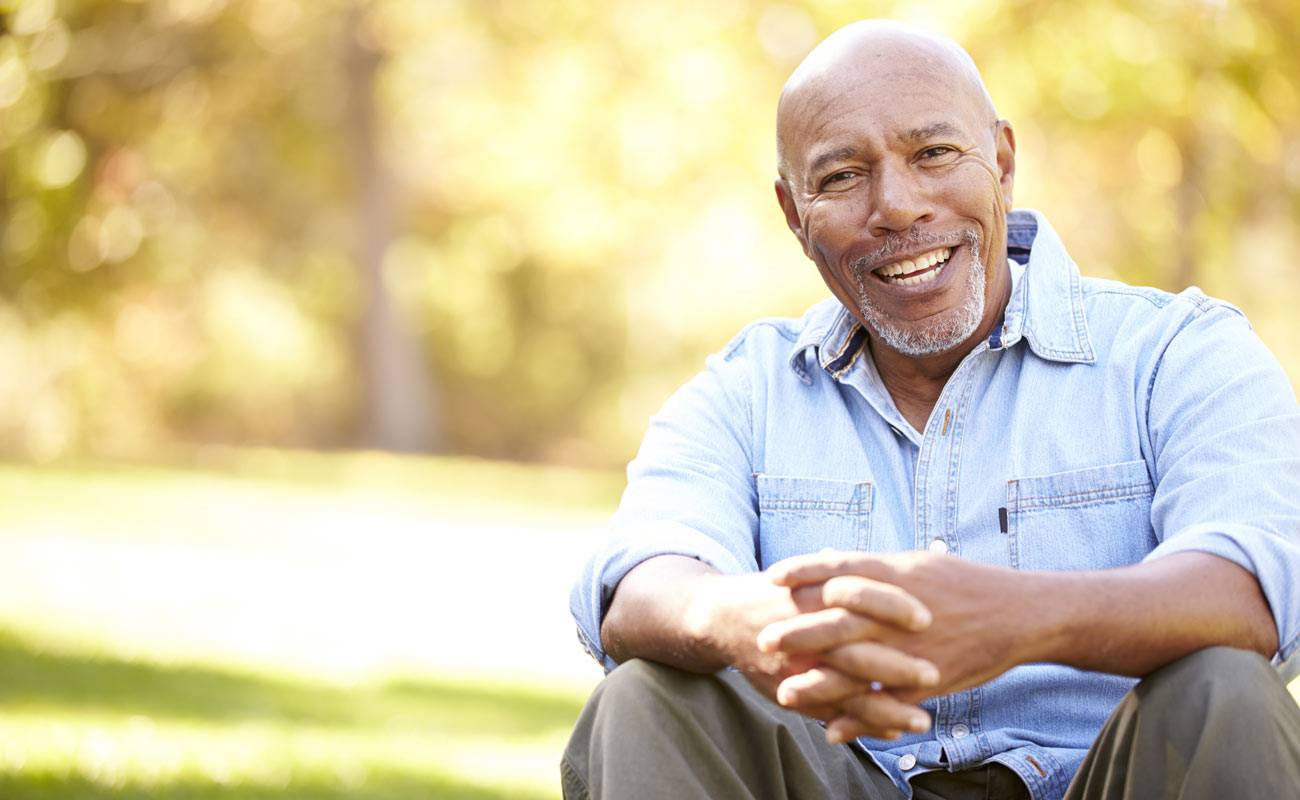 Smiling African-American man with gray goatee seated in autumn park with clasped hands and denim shirt.