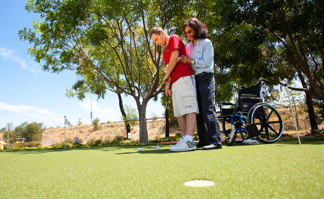 Man wearing shorts and a red shirt practices a golf swing with the assistance of a physical rehabilitation specialist.