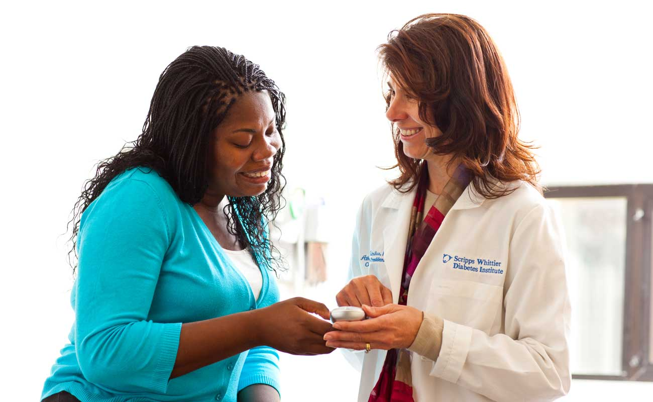A patient with diagnosed with diabetes shares a friendly conversation with a Scripps researcher as part of a clinical study.
