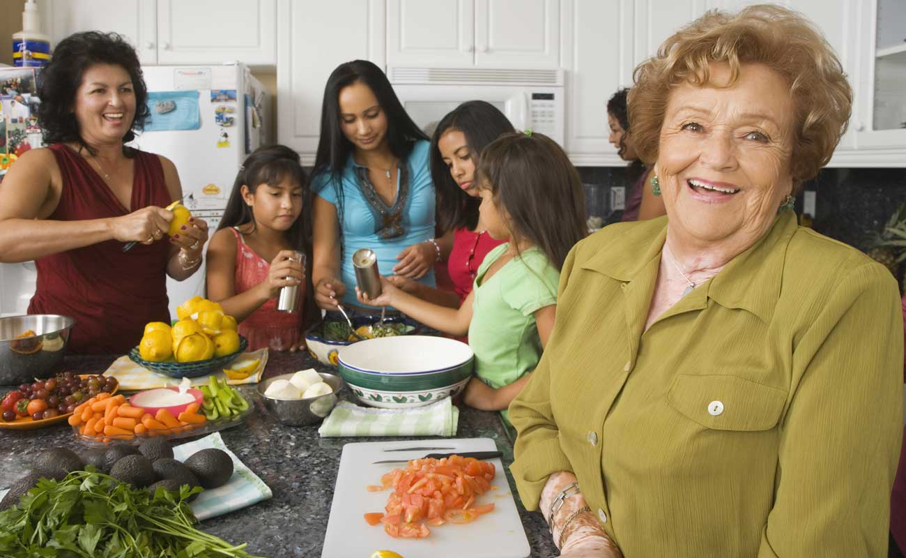A large happy family gathers together in a kitchen setting to prepare a health meal