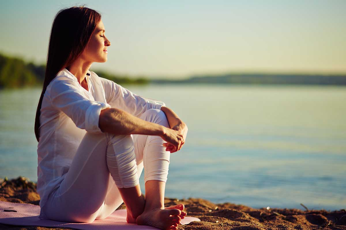 Woman meditating on the beach in a tranquil sunset setting.