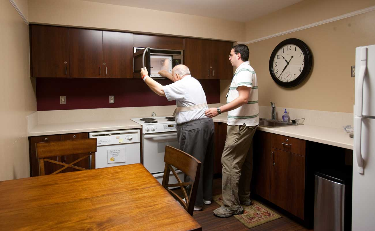 An elderly man opens a microwave door in a physical rehabilitation staged kitchen with the help of a medical professional.